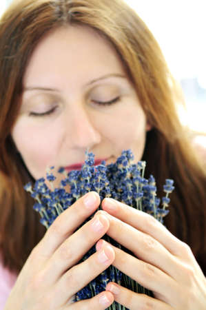 Mature woman smelling lavender flowers - focus on hands photo