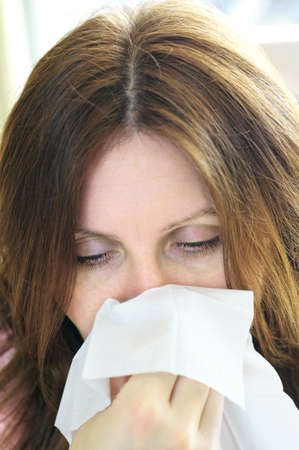Mature woman with a flu or an allergy symptoms photo