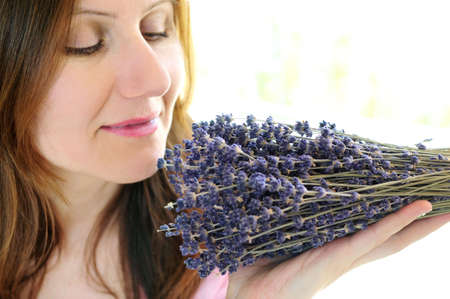 Mature woman smelling bunch of dried lavender photo