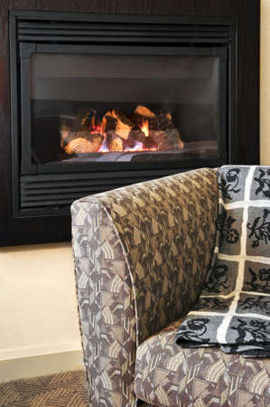 gas fireplace: Fireplace and cozy armchair in living room