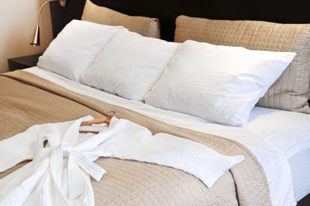 Comfortable bed with clean bathrobe in upscale hotel Stock Photo