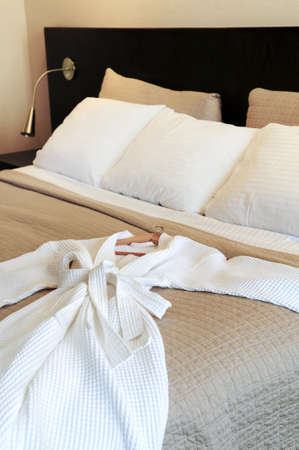 upscale: Comfortable bed with clean bathrobe in upscale hotel Stock Photo