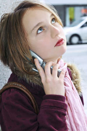 sidewalk talk: Teenage girl talking on cell phone outside
