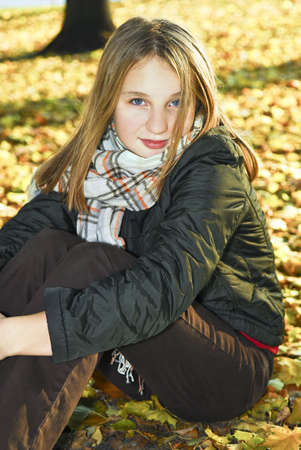 Portrait of a beautiful teenage girl in fall park photo