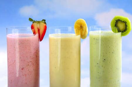 batidos de frutas: Surtido de frutas y bayas smoothies sobre fondo azul cielo
