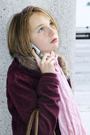 Teenage girl talking on cell phone outside