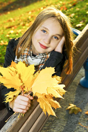 Portrait of a beautiful teenage girl in fall park