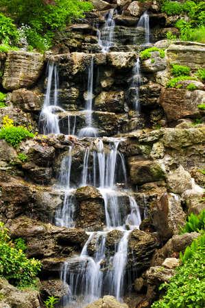 Cascading waterfall in japanese garden in springtime photo