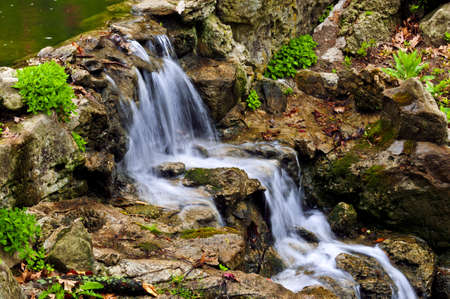Cascading waterfall in japanese garden in springtime photo