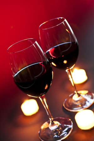 Two wineglasses with red wine at candlelight photo