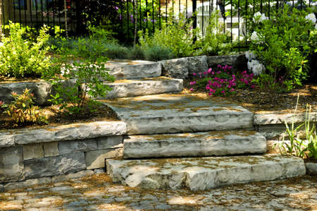 Landscaped front yard with natural stone steps and walkway photo