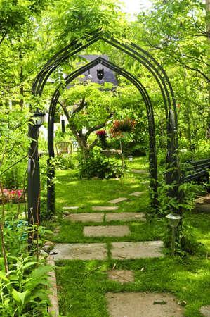 Lush green garden with wrought iron arbor photo