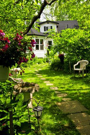 Camino de remojo de piedras conduce a una casa en un frondoso jardín verde  Foto de archivo