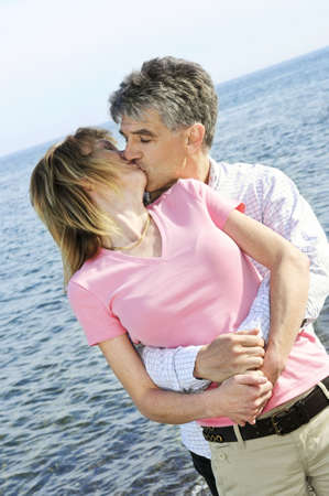 boomers: Mature romantic couple of  boomers kissing on a beach