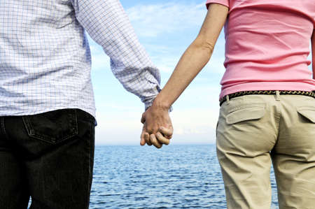 Mature romantic couple holding hands on the beach photo