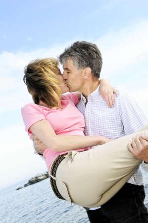 Ouder romantische paar van boomers zoenen op een strand