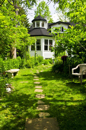 path cottage garden: Path of steeping stones leading to a house in lush green garden Stock Photo