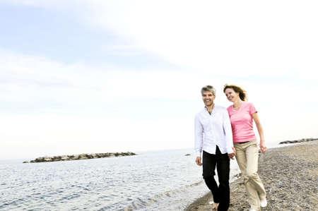 Mature romantic couple walking on a beach photo
