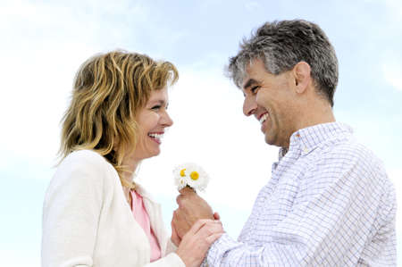 Mature couple enjoying a  moment with flowers photo