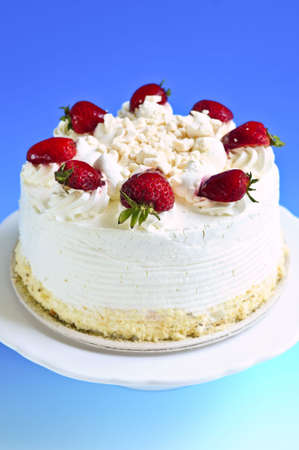 Strawberry meringue cake on a plate on blue background Stock Photo