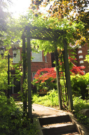 Landscaped front yard of a house with flowering garden and arbor. Lens flare is intentional. Stock Photo - 3267844