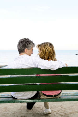 Mature romantic couple on a bench on seashore photo