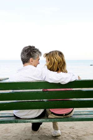 Mature romantic couple on a bench on seashore photo