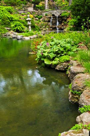 Cascada cascada y el estanque en el jardín japonés