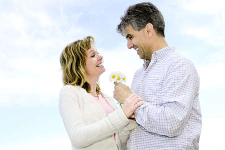Mature couple enjoying a romantic moment with flowers photo