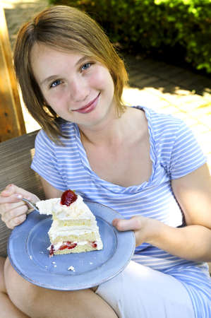 Teenage girl eating a piece of strawberry cake photo