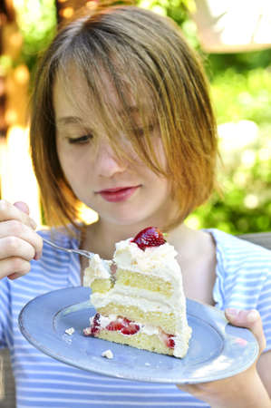 indulging: Teenage girl eating a piece of strawberry cake Stock Photo
