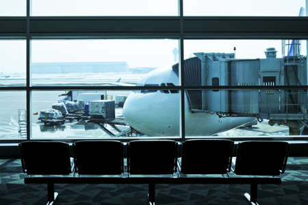 wait: Waiting area of airport gate with airplane outside
