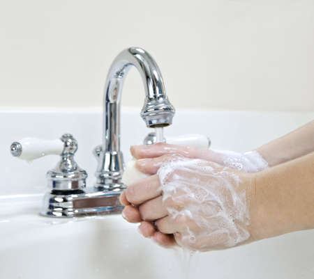 Child washing hands with soap under running water