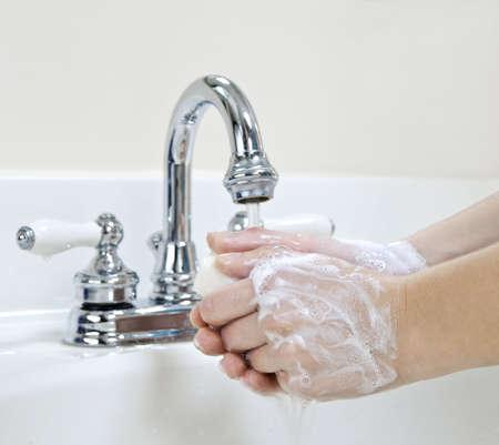 Child wassen van de handen met zeep onder stromend water