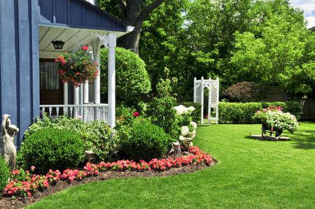 조 경된 앞뜰에는 꽃과 녹색 잔디가 있습니다.