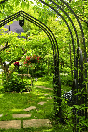 bower: Lush green garden with wrought iron arbor
