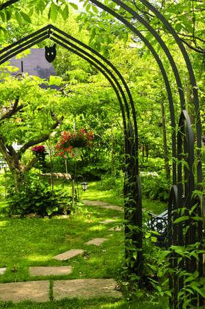 cottage garden: Lush green garden with wrought iron arbor