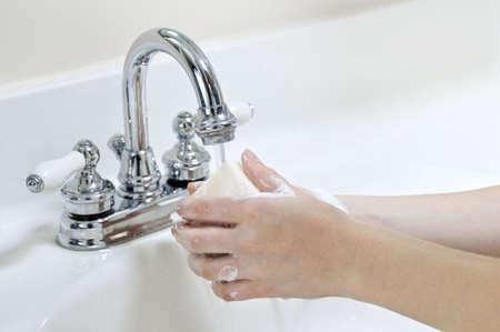 Niño lavándose las manos con jabón bajo el chorro de agua  Foto de archivo - 3480381