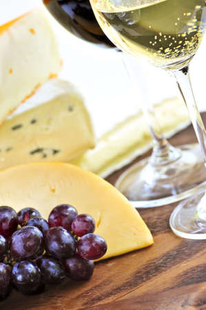 Wineglasses with red and white wine and assorted cheeses photo
