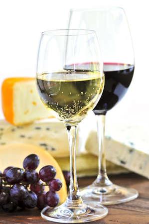 Wijnglazen met rode en witte wijn en een assortiment kazen Stockfoto