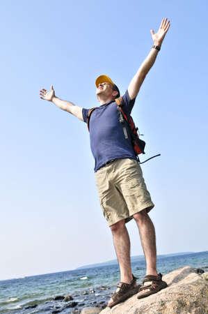 Middle aged hiker standing on top of a mountain raising his arms Stock Photo - 3492976