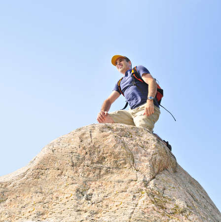 Middle aged man with backpack climbing a rock Stock Photo - 3492984