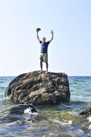1 person: Man stranded on a rock in ocean calling for help Stock Photo