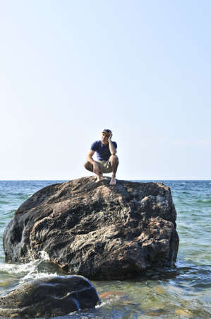 awaiting: Man stranded on a rock in ocean waiting for rescue Stock Photo