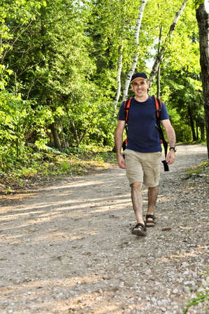 Happy middle aged man walking on a forest trail Stock Photo