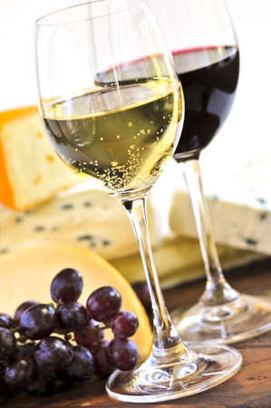 cheeses: Wineglasses with red and white wine and assorted cheeses