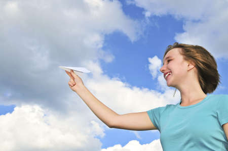 Young teenage girl holding a paper airplane photo