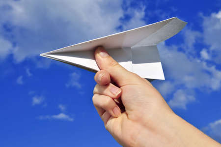 Childs hand holding a paper airplane on blue sky background photo