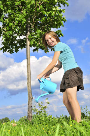 ing: Teenage girl ing a young tree on blue sky background
