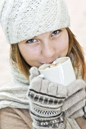 winter: Teenage girl in winter hat with cup of hot chocolate Stock Photo